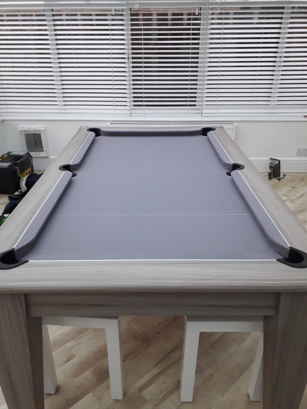 Recover of a Gatley pool dining table in a silver napped wool cloth